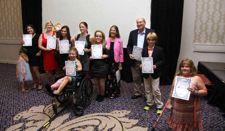 Dr. John Herzenberg with multiple patients, one using forearm crutches and one in a wheelchair, and a few of their family members holding award certificates at Rubin Institute for Advanced Orthopedics 2016 Save-A-Limb Fund Dinner