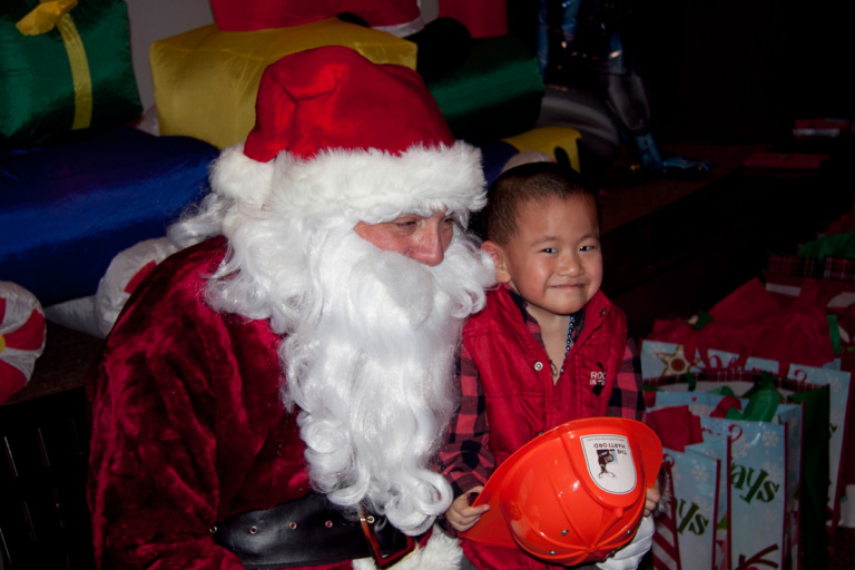 Young boy with fireman hat sits on Santa's lap at the International Center for Limb Lengthening pediatric holiday party