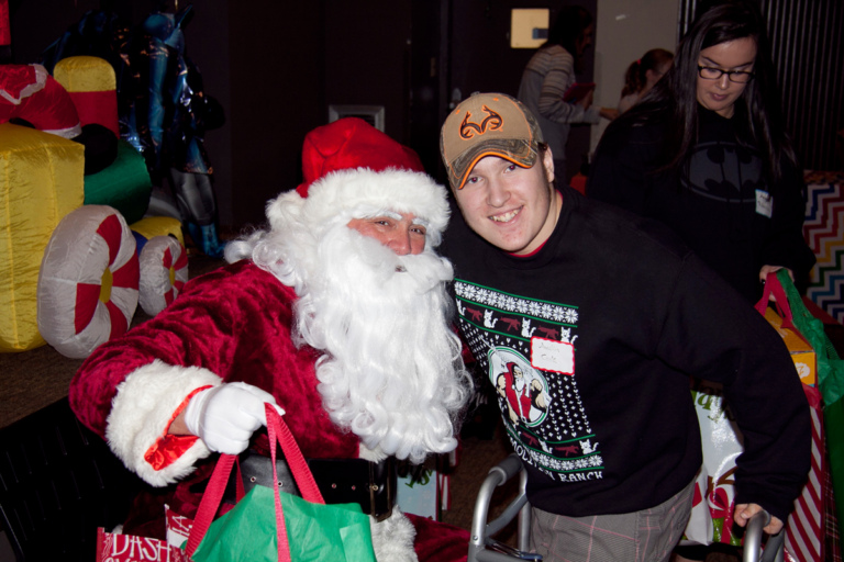 Boy with walker poses for a picture with Santa at the International Center for Limb Lengthening pediatric holiday party