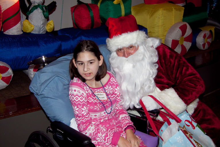Girl in wheelchair takes a picture with Santa at the International Center for Limb Lengthening pediatric holiday party