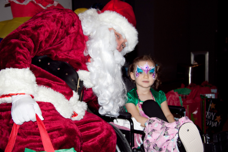 Young girl in a wheelchair with face painted has picture taken with Santa at the International Center for Limb Lengthening pediatric holiday party