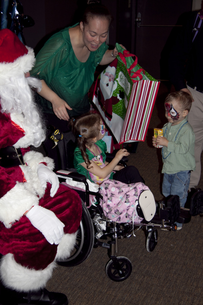 Young girl in a wheelchair receives a present from Santa at the International Center for Limb Lengthening pediatric holiday party