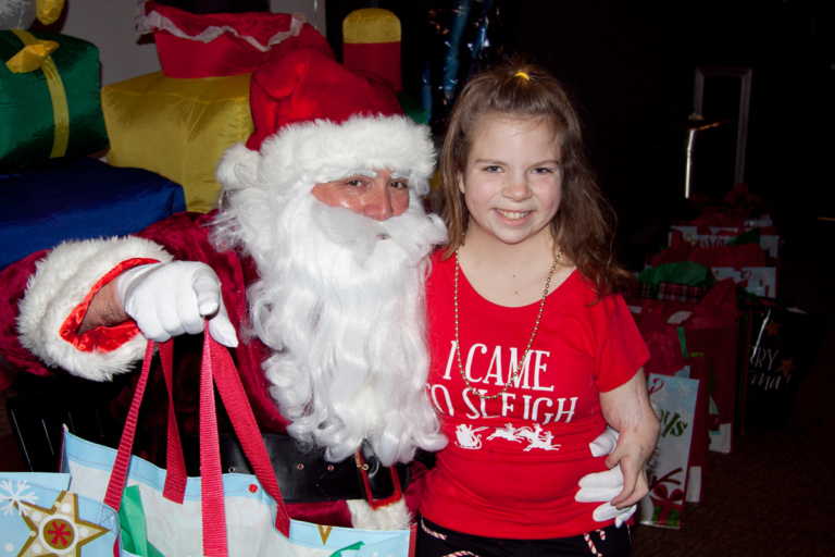 Girl patient takes picture with Santa and present at the International Center for Limb Lengthening pediatric holiday party