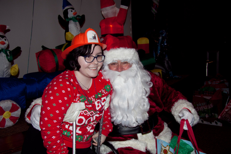Girl on crutches and with a fireman hat on takes picture with Santa at the International Center for Limb Lengthening pediatric holiday party