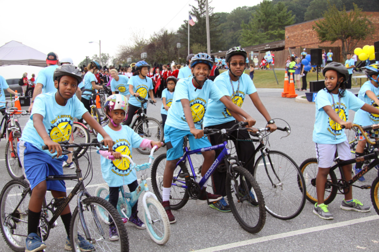 5 children in Save-A-Limb blue event shirts on bikes at Rubin Institute for Advanced Orthopedics 2016 Save-A-Limb Fund Event