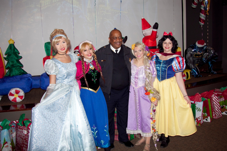 Firemen takes picture with Disney princesses, Cinderella, Anna, Rapunzel, and Snow White at the International Center for Limb Lengthening pediatric holiday party