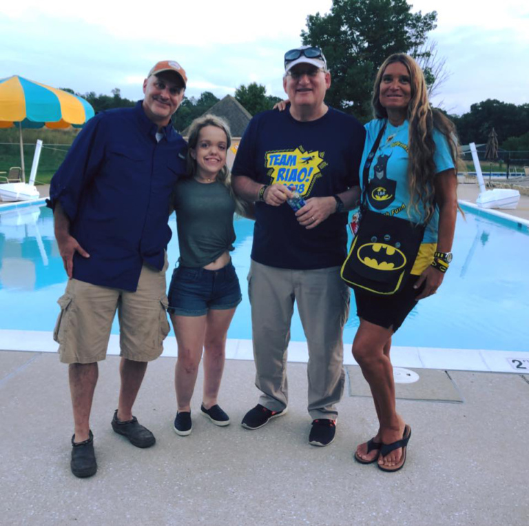 Dr. Shawn Standard, Dr. John Herzenberg, Pediatric Liaison Marilyn Richardson and female patient pose in front of pool at Rubin Institute for Advanced Orthopedics 2018 Save-A-Limb Pool Party event