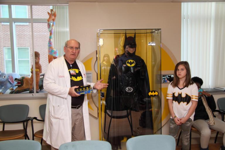 """Dr. John Herzenberg speaks in front of Leonard B. """"Batman"""" Robinson's Batman suit in glass case at the International Center for Limb Lengthening's Leonard B. """"Batman"""" Robinson Memorial Valentine's Day Party"""
