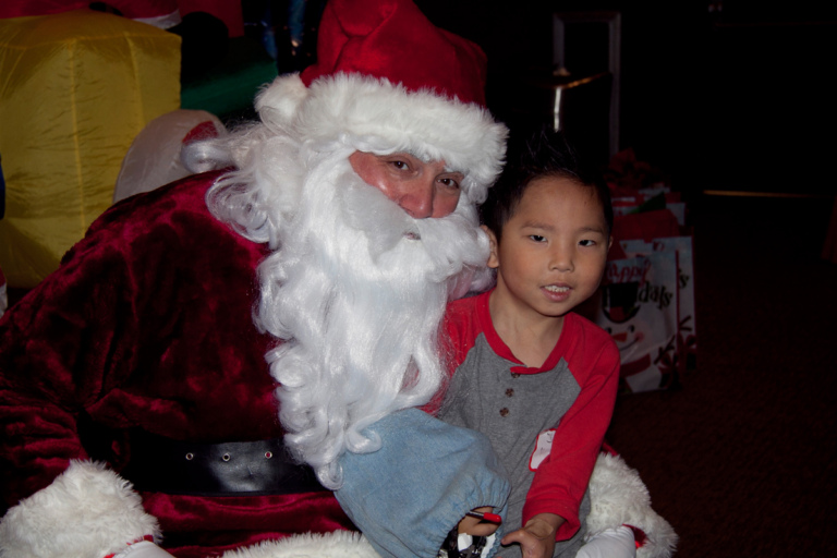 Young boy with covered external fixator on arm sits on Santa's lap for a picture at the International Center for Limb Lengthening pediatric holiday party