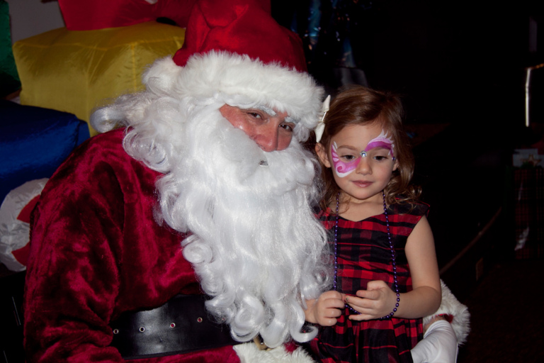 Young girl with pink face painting takes picture with Santa at the International Center for Limb Lengthening pediatric holiday party