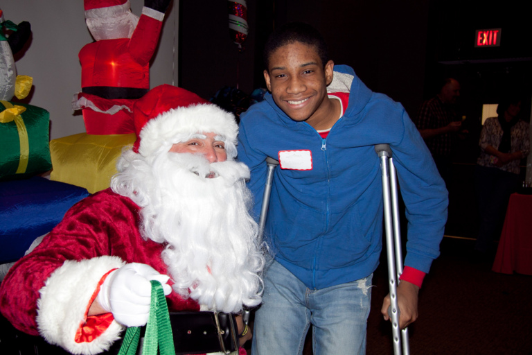 Boy with crutches smiles for a photo with Santa at the International Center for Limb Lengthening pediatric holiday party