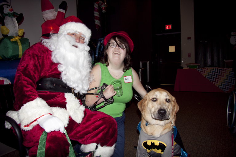 Girl with fixators on both arms takes photo with Santa and service dog dressed as Batman at the International Center for Limb Lengthening pediatric holiday party