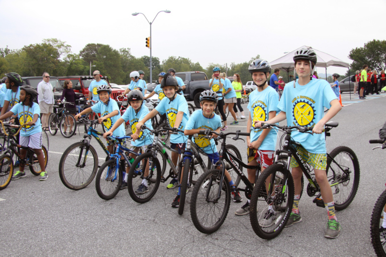 6 children in Save-A-Limb blue event shirts on bikes at Rubin Institute for Advanced Orthopedics 2016 Save-A-Limb Fund Event