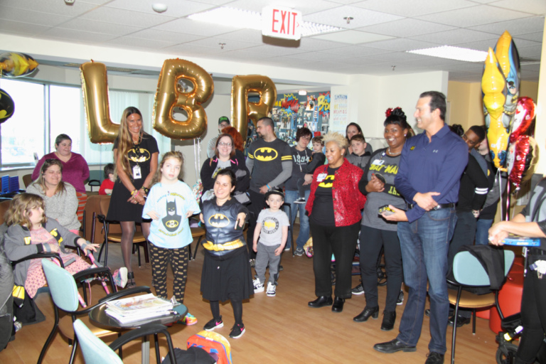 "Patients of all ages, families and staff gather in the clinic waiting room with large gold L.B.R. balloons at the International Center for Limb Lengthening's Leonard B. ""Batman"" Robinson Memorial Valentine's Day Party"