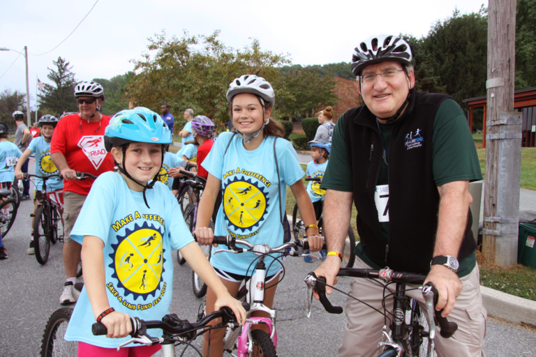 Dr. John Herzenberg on bike with 2 young girls on bikes at Rubin Institute for Advanced Orthopedics 2016 Save-A-Limb Fund Event