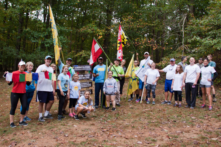 Earl Cole, the winner of Survivor: Fiji reality television show and founder of Perthes Kids Foundation, Dr. Shawn Standard and Dr. John Herzenberg pose with participants of the hike challenge at the top of the summit with flags Rubin Institute for Advanced Orthopedics 2017 Save-A-Limb Fund Event