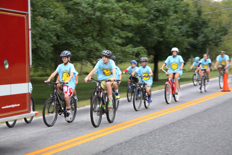 Several bike riders follow behind fire truck at Rubin Institute for Advanced Orthopedics 2016 Save-A-Limb Fund Event
