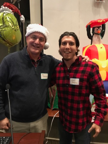 Dr. Shawn Standard wearing a Santa hat and young man pose for a picture at the International Center for Limb Lengthening pediatric holiday party