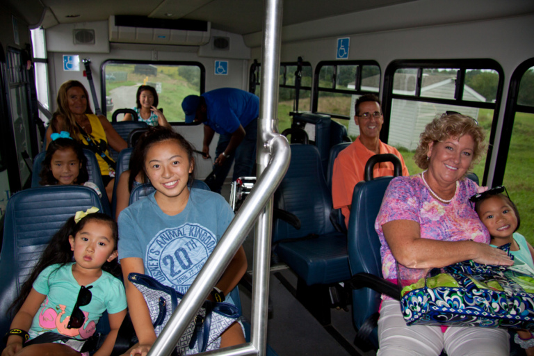 Mother, father and five girls ride shuttle bus with Pediatric Liaison Marilyn Richardson at Rubin Institute for Advanced Orthopedics 2018 Save-A-Limb Pool Party event
