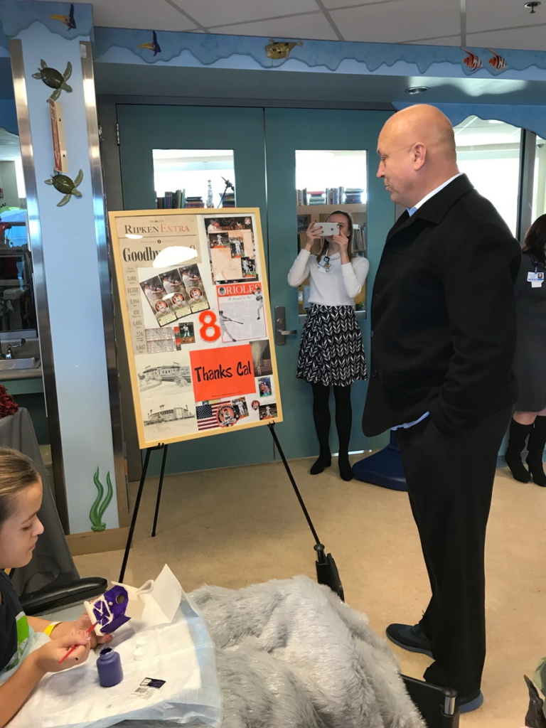 Cal Ripken looks at poster while young girl patient in wheelchair paints a birdhouse at Cal Ripken at Herman & Walter Samuelson Children