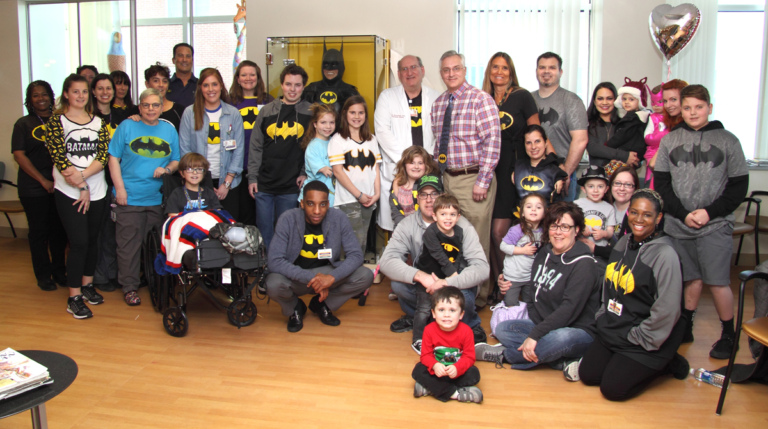 "Dr. Shawn Standard and Dr. John Herzenberg pose with a large group of patients, family members and staff, mostly wearing Batman shirts, in front of the glass case with Batman costume at the International Center for Limb Lengthening's Leonard B. ""Batman"" Robinson Memorial Valentine's Day Party"