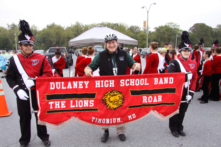 Dr. John Herzenberg pointing at Dulaney High School Band marching band banner at Rubin Institute for Advanced Orthopedics 2016 Save-A-Limb Fund Event