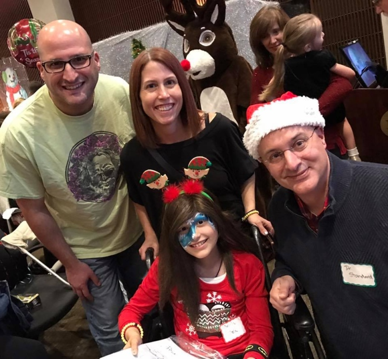 Dr. Shawn Standard in Santa hat, mother, father and young girl with face painted in a wheelchair at the International Center for Limb Lengthening pediatric holiday party