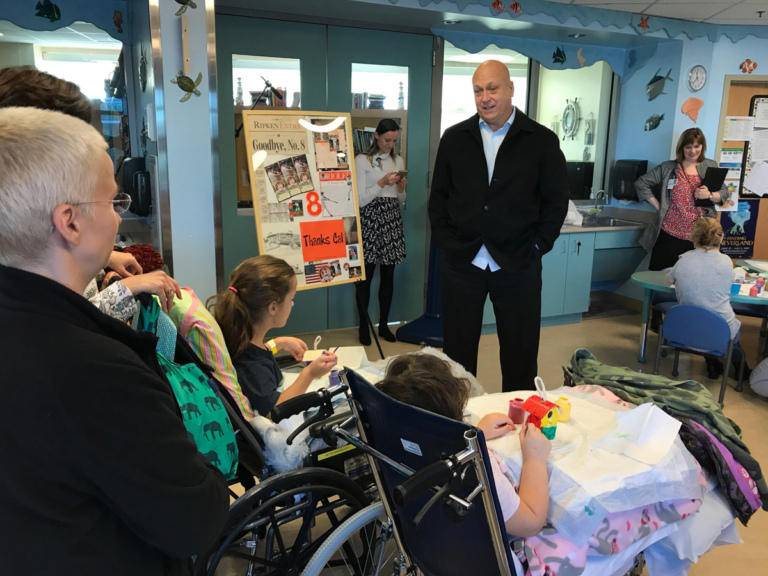 Cal Ripken talks to 2 young girl patients in wheelchairs at Cal Ripken at Herman & Walter Samuelson Children