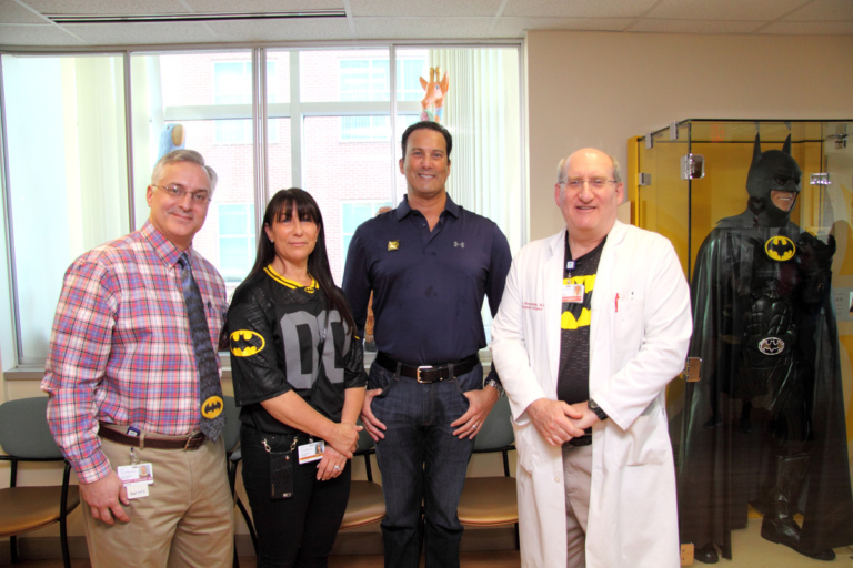 "Dr. Shawn Standard and Dr. John Herzenberg pose with the family of Leonard B. ""Batman"" Robinson by glass case with Batman costume at the International Center for Limb Lengthening's Leonard B. ""Batman"" Robinson Memorial Valentine's Day Party"
