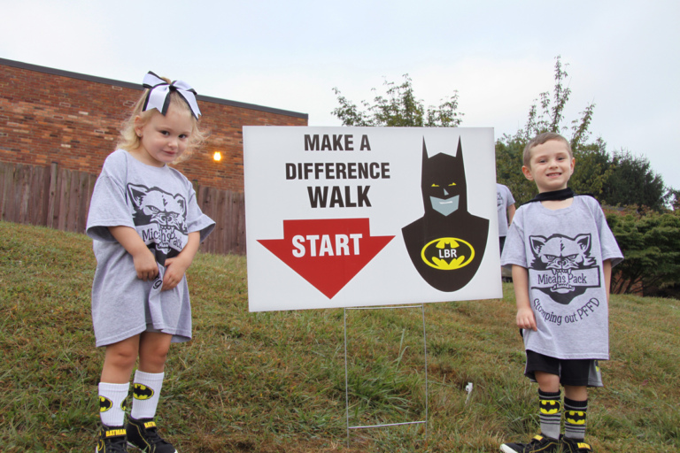 "2 young children wearing Batman attire standing with Batman ""Make a Difference Walk"" starting sign at Rubin Institute for Advanced Orthopedics 2016 Save-A-Limb Fund Event"