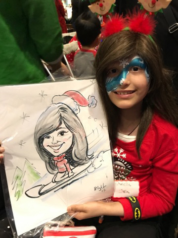 Young girl in wheelchair with face painted holding up her caricature at the International Center for Limb Lengthening pediatric holiday party