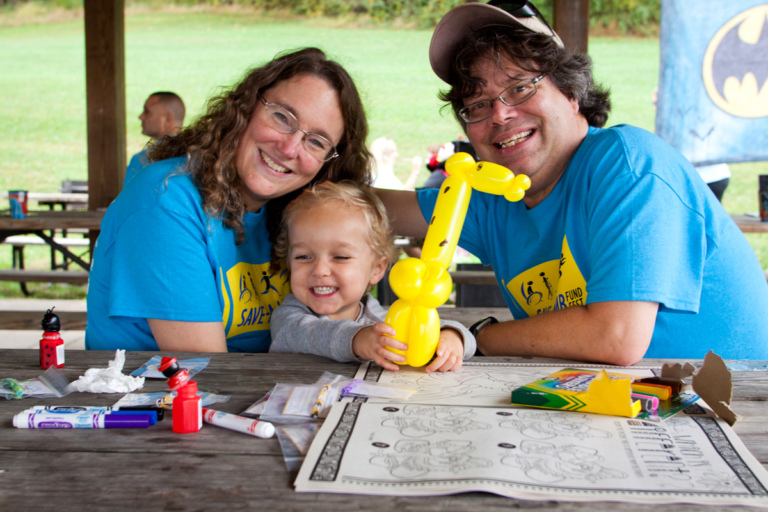 Young child holds yellow balloon animal with parents under a pavilion at Rubin Institute for Advanced Orthopedics 2017 Save-A-Limb Fund Event