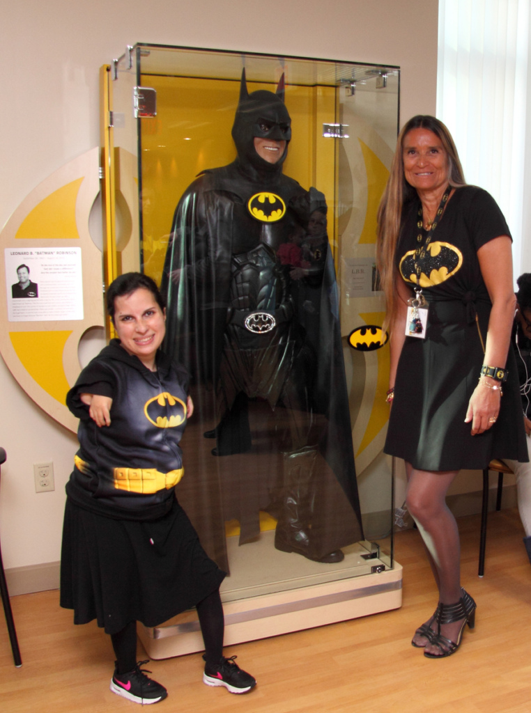 "Marilyn Richardson, Pediatric Liaison, and young woman patient both wearing Batman dresses take photo in front of glass case with Lenny B. Robinson's Batman suit at the International Center for Limb Lengthening's Leonard B. ""Batman"" Robinson Memorial Valentine's Day Party"