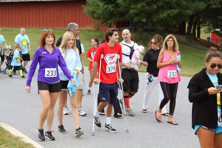 "Boy with crutches walking among other walkers in the ""Make a Difference Walk"" at Rubin Institute for Advanced Orthopedics 2016 Save-A-Limb Fund Event"