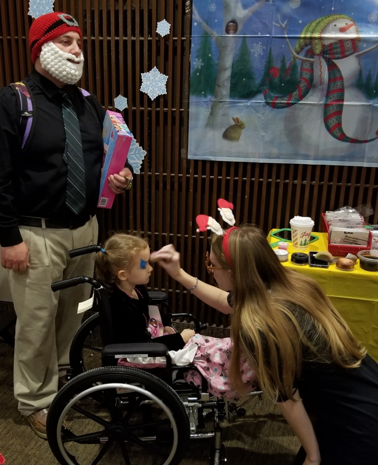 Young girl in wheelchair gets her face painted at the International Center for Limb Lengthening pediatric holiday party
