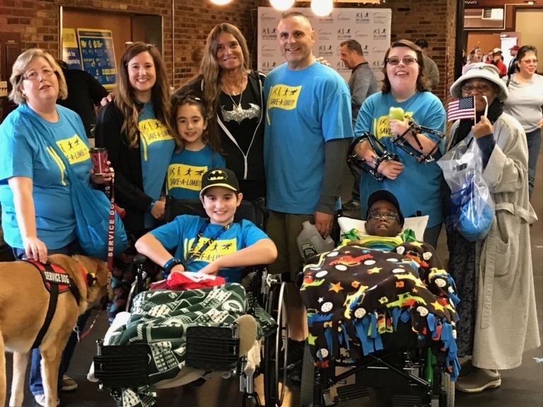 Pediatric Liaison Marilyn Richardson poses for a picture with parents, girl with 2 external fixators on her arms, 2 boys in wheelchairs, a young girl and a service dog at Rubin Institute for Advanced Orthopedics 2017 Save-A-Limb Fund Event