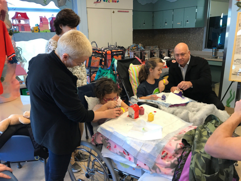 Cal Ripken helps 2 young girl patients in wheelchairs paint birdhouses at Cal Ripken at Herman & Walter Samuelson Children