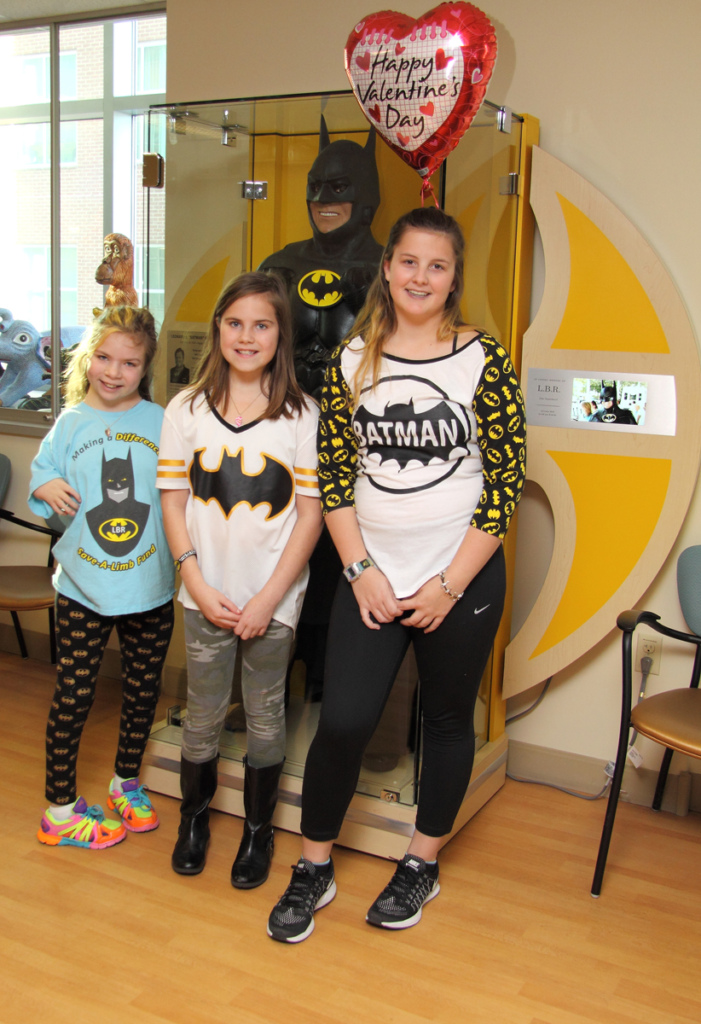 "3 young girls take photo in front of glass case with Lenny B. Robinson's Batman suit and Happy Valentine's Day heart balloon at the International Center for Limb Lengthening's Leonard B. ""Batman"" Robinson Memorial Valentine's Day Party"