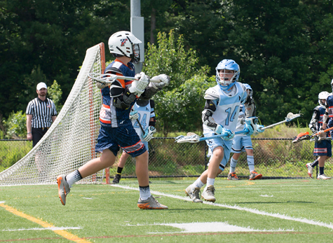 CJ in uniform number 14 with a lacrosse stick playing defense against a player om the opposing team near the goal on the playing field