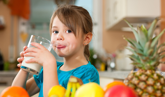 Child drinking milk with fresh fruit on table in kitchen