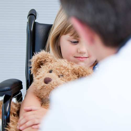 Doctor talking to a little girl in a wheelchair holding a teddy bear to help her manage her pain after surgery