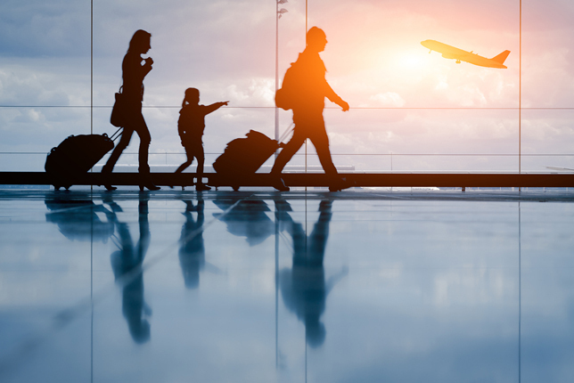 Silhouette of a family in an airport preparing to board an airplane