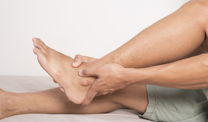 Man with foot and ankle arthritis holding his ankle