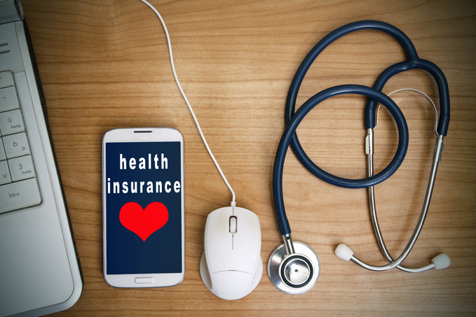 Health insurance on a tablet with a computer mouse and a stethoscope