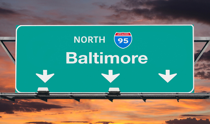 Highway sign for Interstate 95 to Baltimore against a cloudy sunset