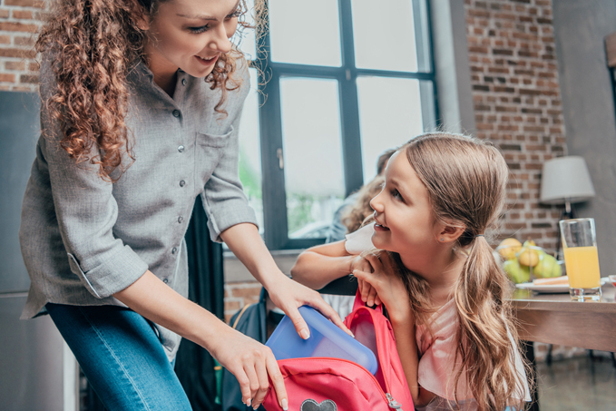 Mother giving school lunch to daughter