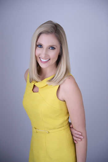 Carly's professional photograph with her standing in a yellow dress