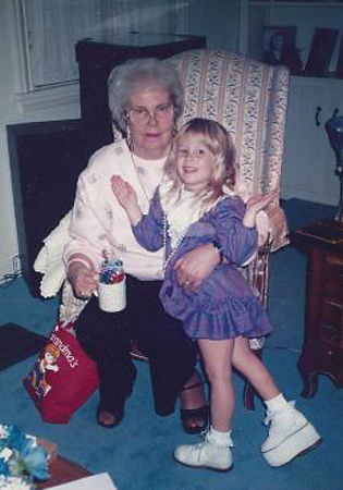 Carly at age 3 or 4 wearing a large shoe lift standing in front of her grandmother sitting in a chair