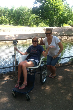 A female friend giving a thumbs up and Carly as a young woman in a wheelchair and holding forearm crutches during internal lengthening
