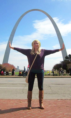 Carly as a young woman with her arms outstretched under St. Louis' Gateway Arch during internal lengthening